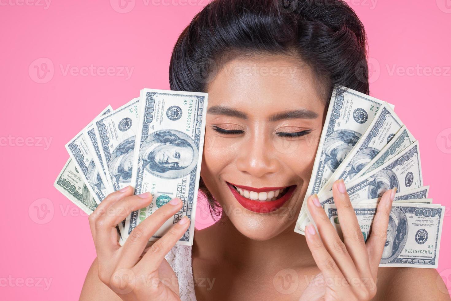 feliz hermosa mujer sosteniendo dólares foto