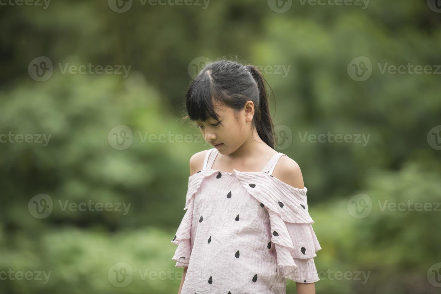 Retrato de una niña asiática caminando en el parque foto