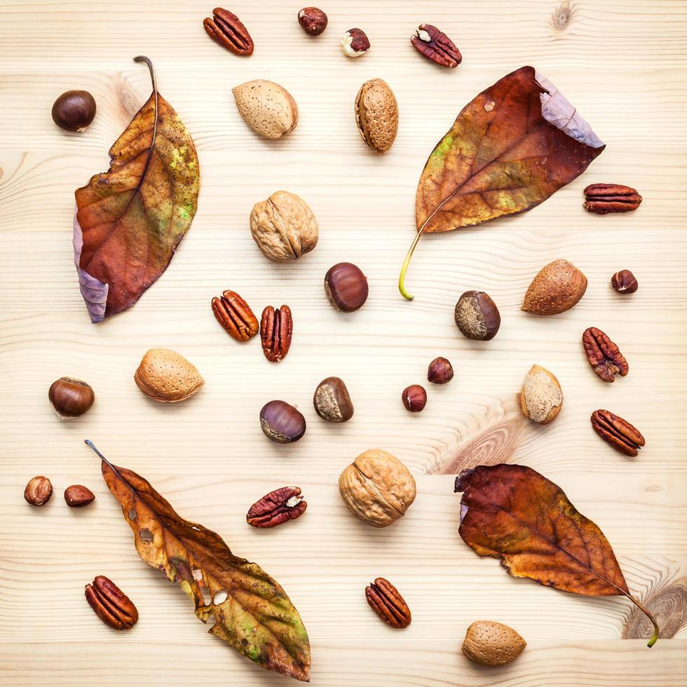 Dried leaves and nuts on a wooden background photo