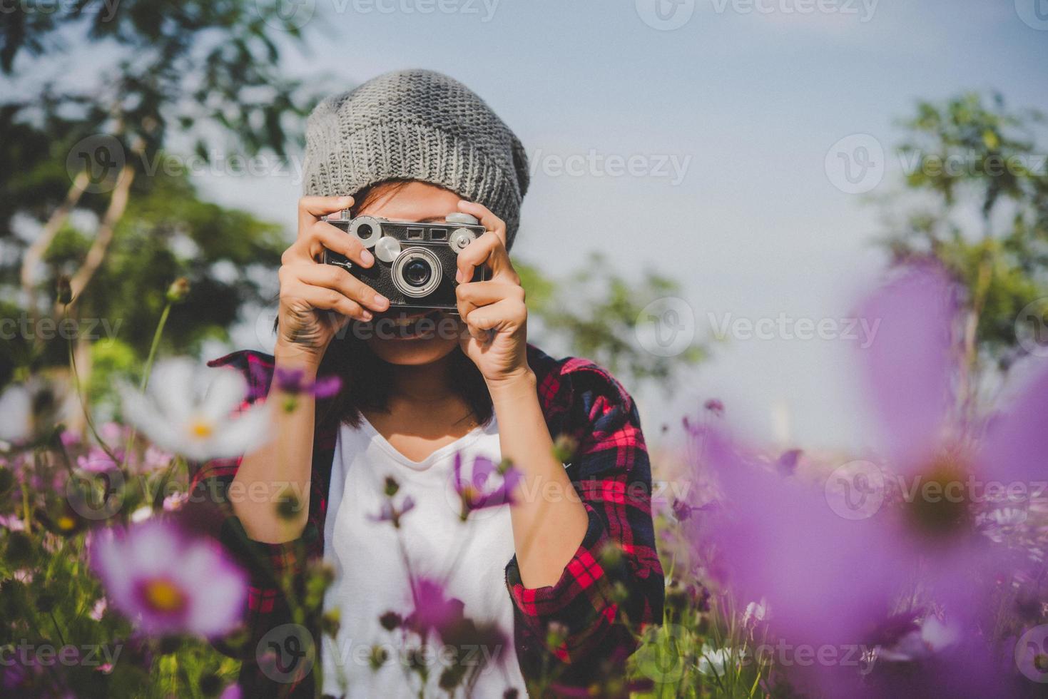 Chica hipster con enfoque de cámara vintage disparando flores en un jardín. foto