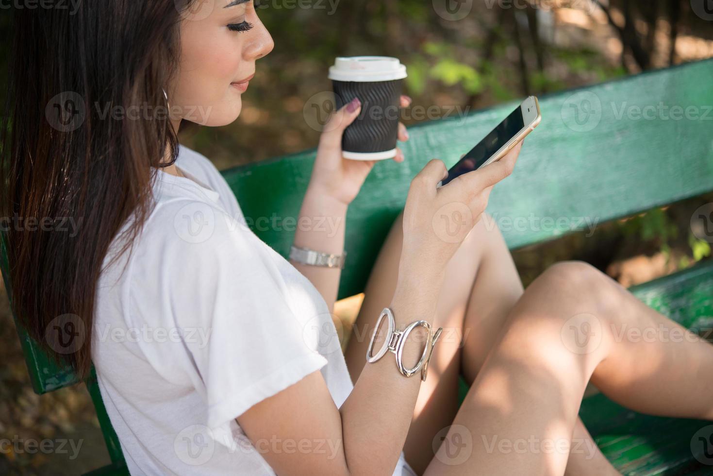 Retrato de una mujer casual feliz sentada en un banco con café y teléfono en el parque foto