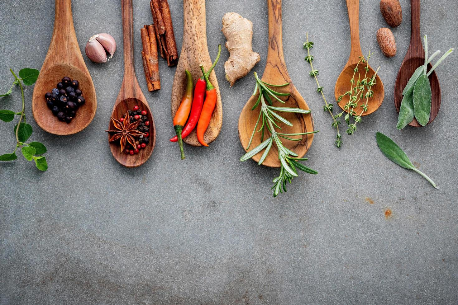 Spices and herbs in wooden spoons photo