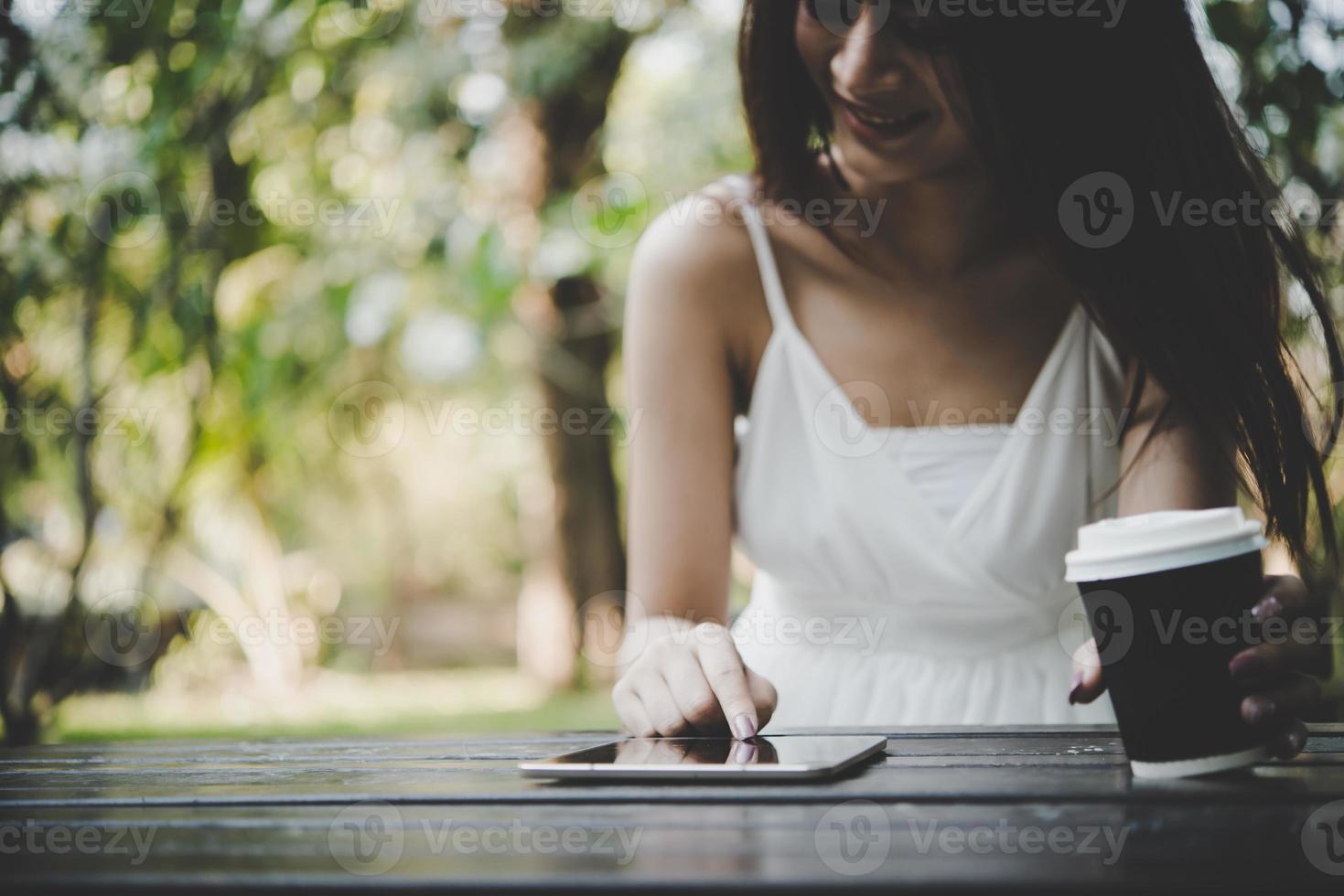 Mujer joven sosteniendo una taza de café desechable mientras envía mensajes de texto a través del teléfono inteligente al aire libre foto