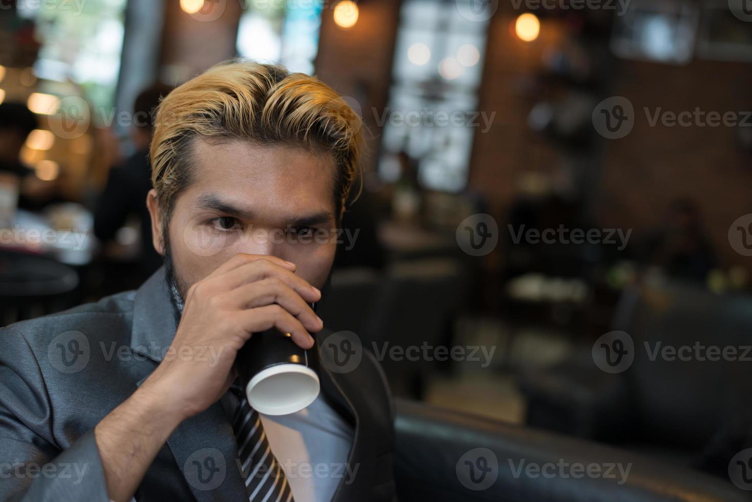 empresario tomando café en la cafetería de la ciudad durante la hora del almuerzo foto