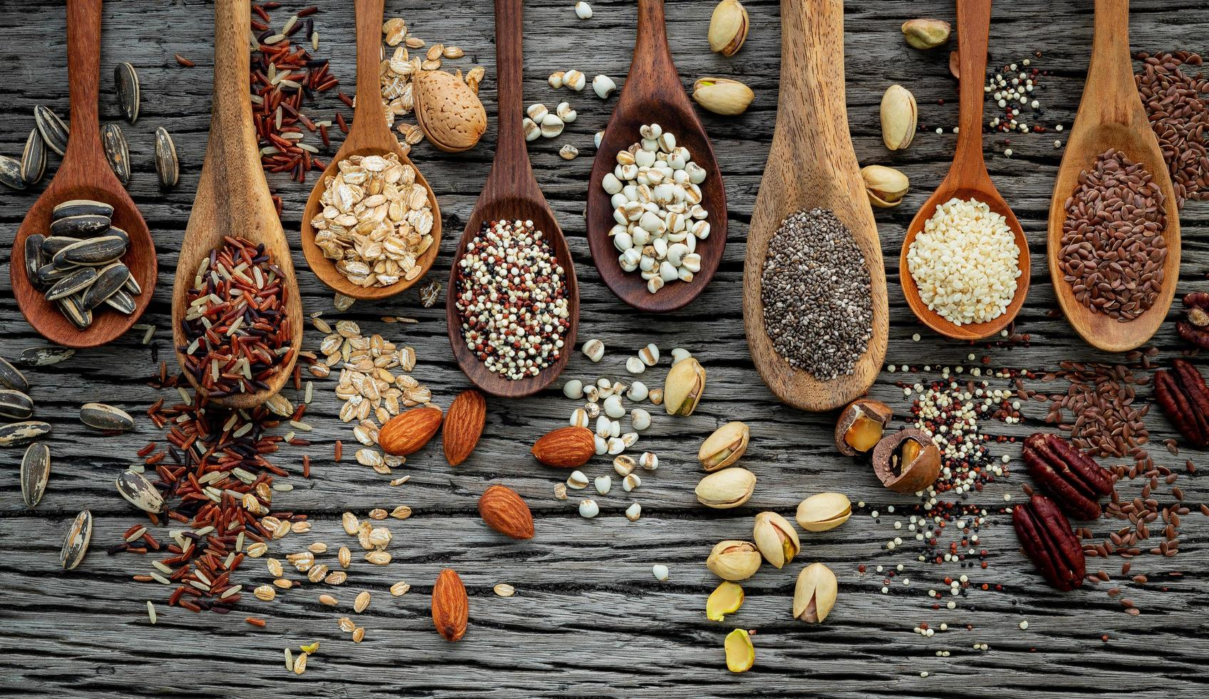 Grains and nuts in spoons on a wooden background photo