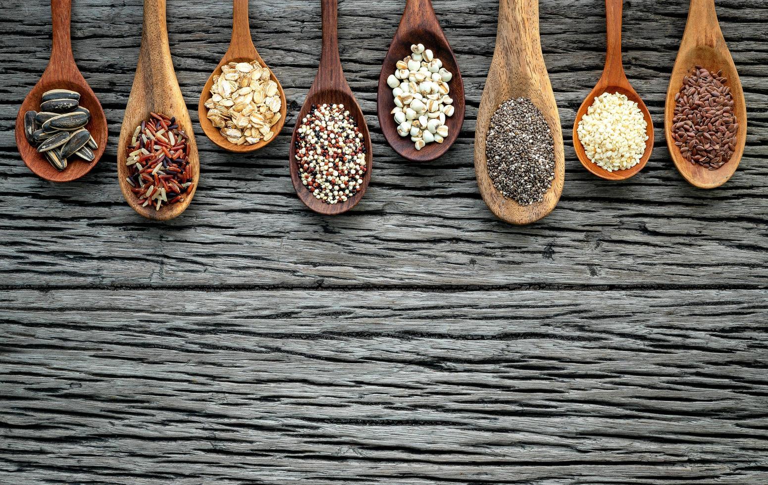 granos surtidos en cucharas de madera foto