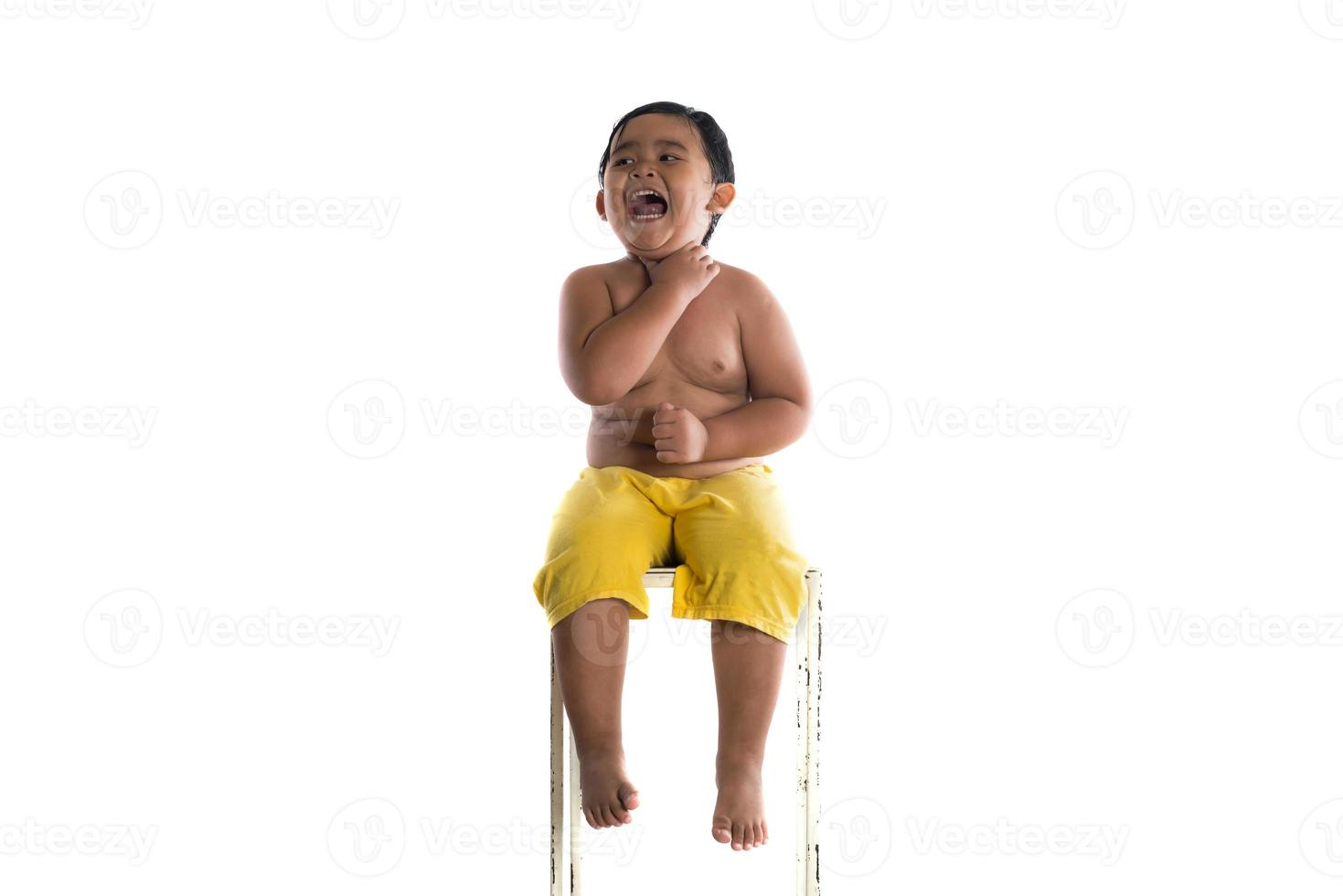 Portrait of a little boy sitting isolated on white background photo