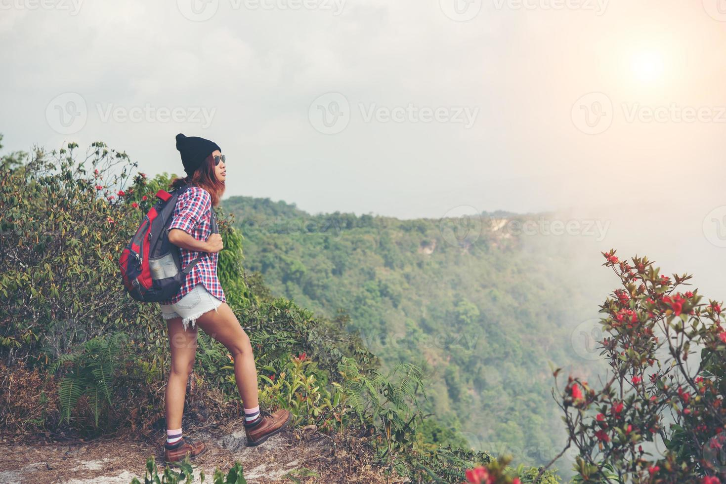 Hiker with backpack standing on top of a mountain and enjoying nature view photo
