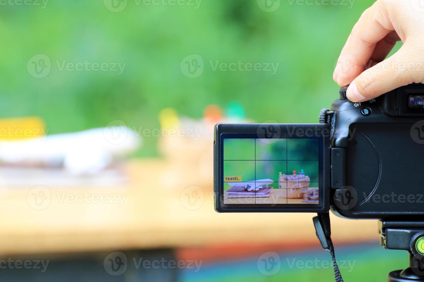 Mano con cámara digital fotografiando configuración de escritorio con aviones y sacos de dinero foto
