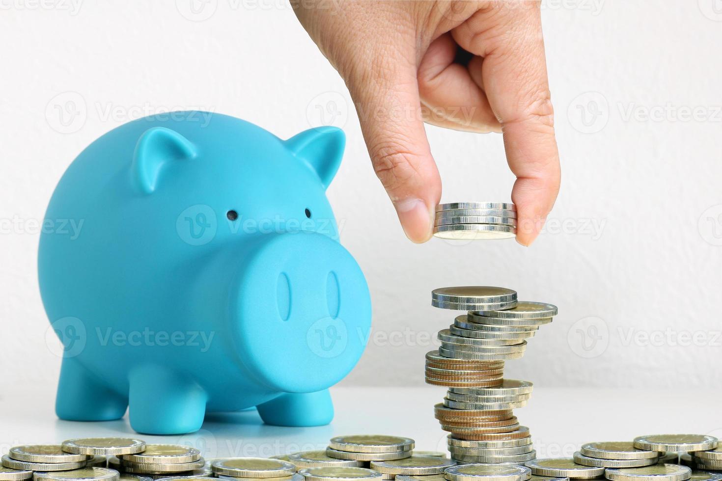 Mano apilando monedas junto a la hucha azul foto