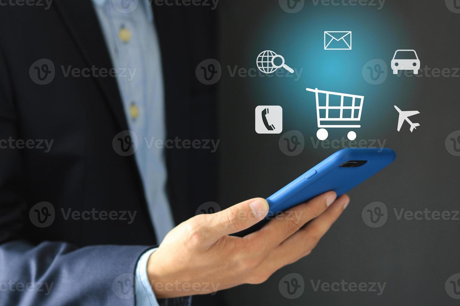 Imagen conceptual del empresario sosteniendo un teléfono celular con iconos de aplicaciones flotantes foto