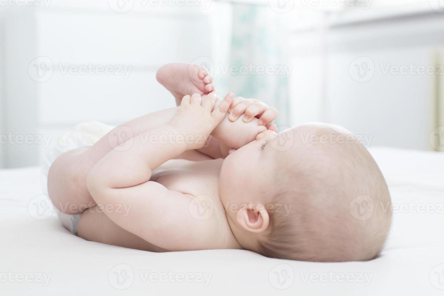 niña acostada y metiéndose la pierna en la boca foto