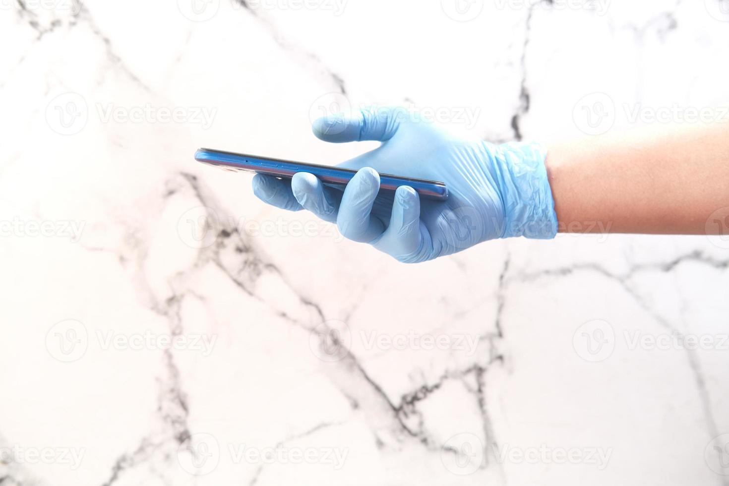 La mano del médico en guantes protectores con un teléfono inteligente. foto