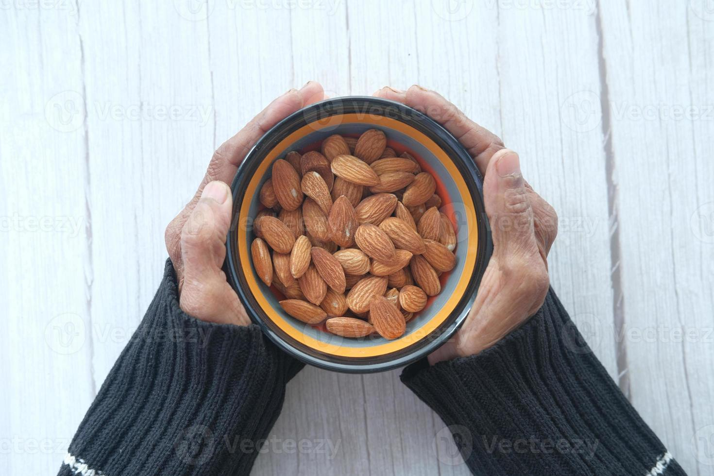 Close-up of senior woman hand holding a bowl on almonds photo