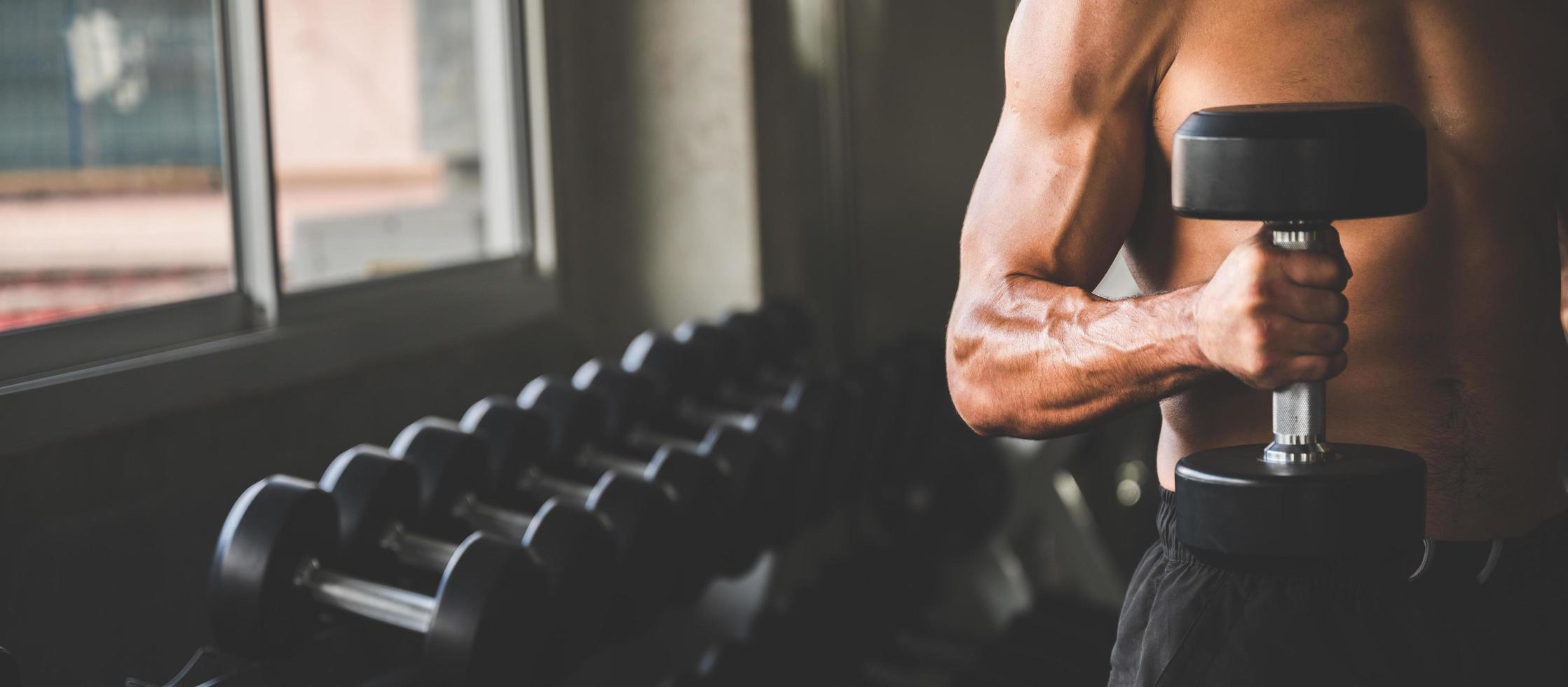Hombre sujetando una pesa en un gimnasio con una fila de pesas en el fondo foto