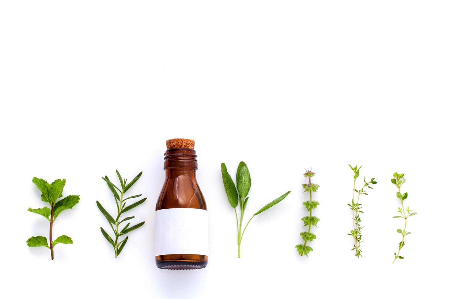botella de aceite esencial con hierbas foto