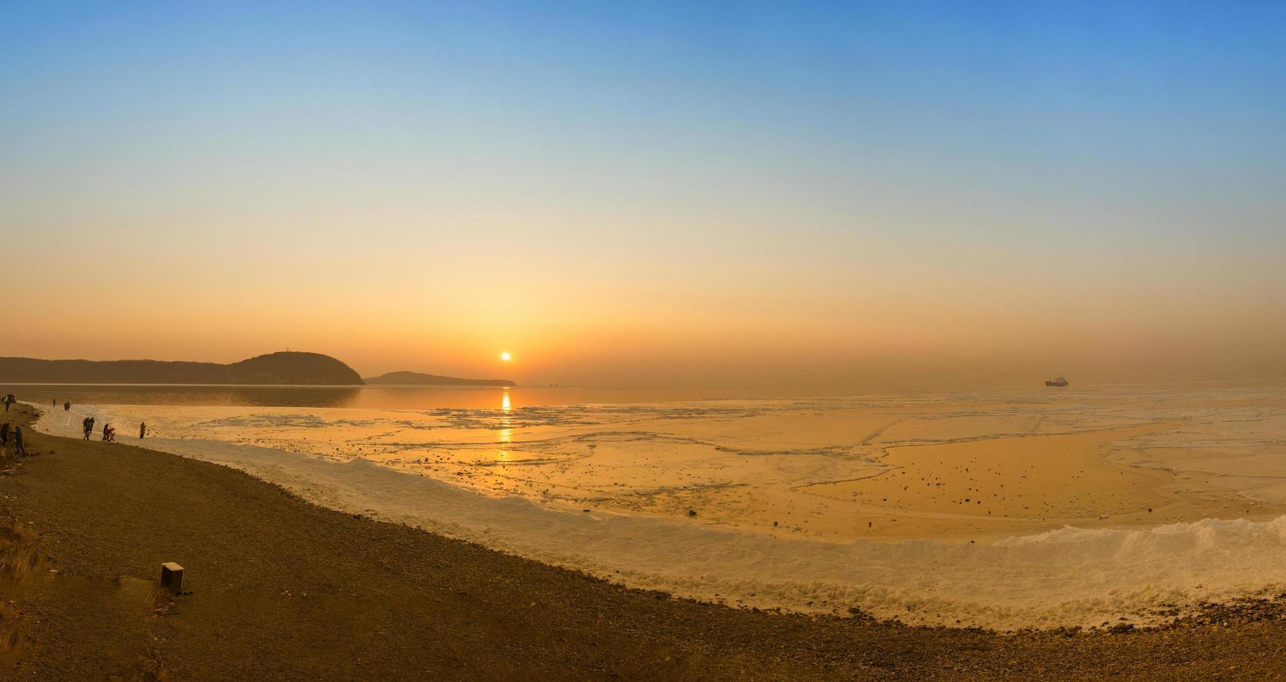 gente en una playa con puesta de sol colorida foto
