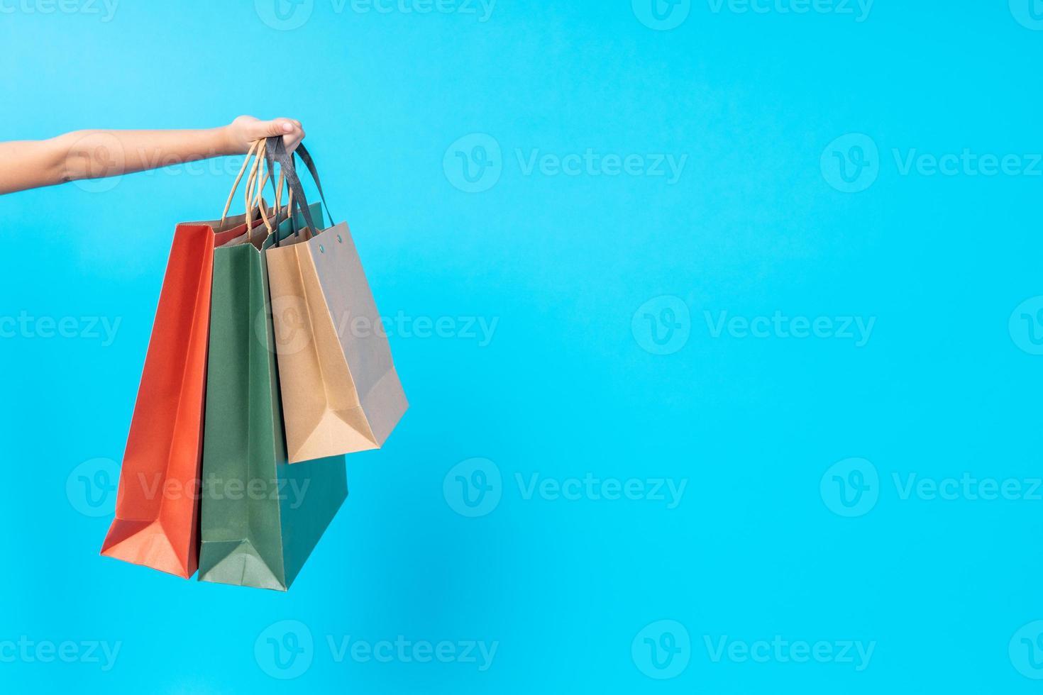 Cerca de la mano que sostiene bolsas de la compra sobre fondo azul. foto