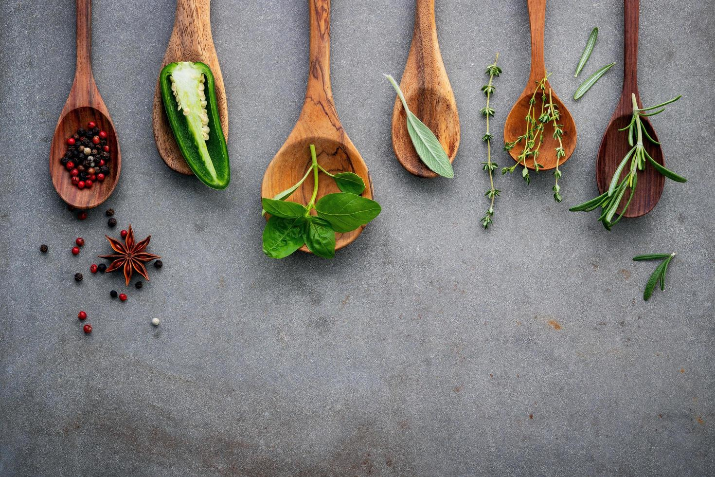 Herbs and spices in spoons on a gray background photo