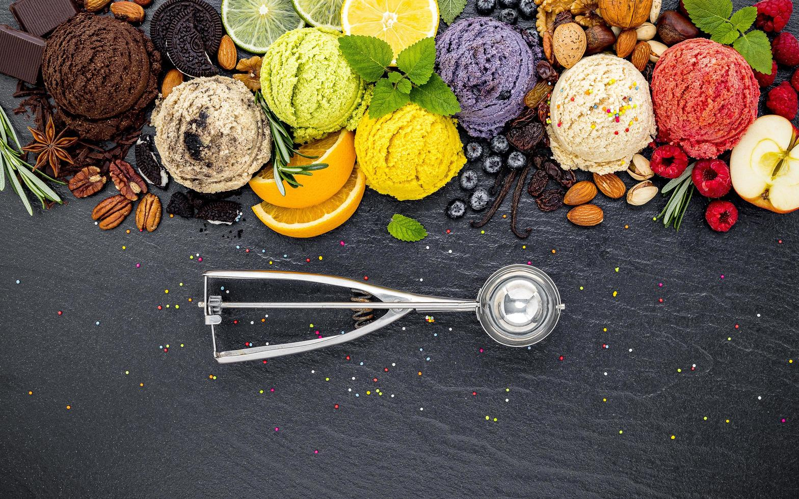 Colorful scoops of ice cream with fruit and an ice cream scoop photo
