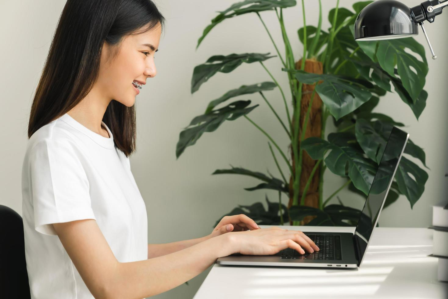 Woman using laptop at home office photo