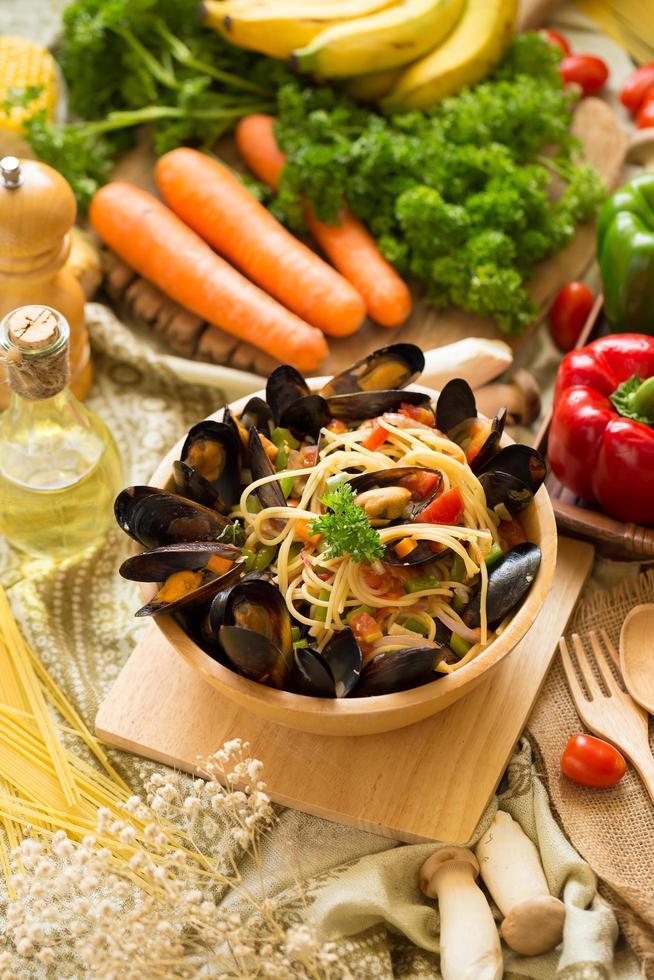 espaguetis y mejillones en un recipiente de madera sobre una tabla de madera junto a verduras foto