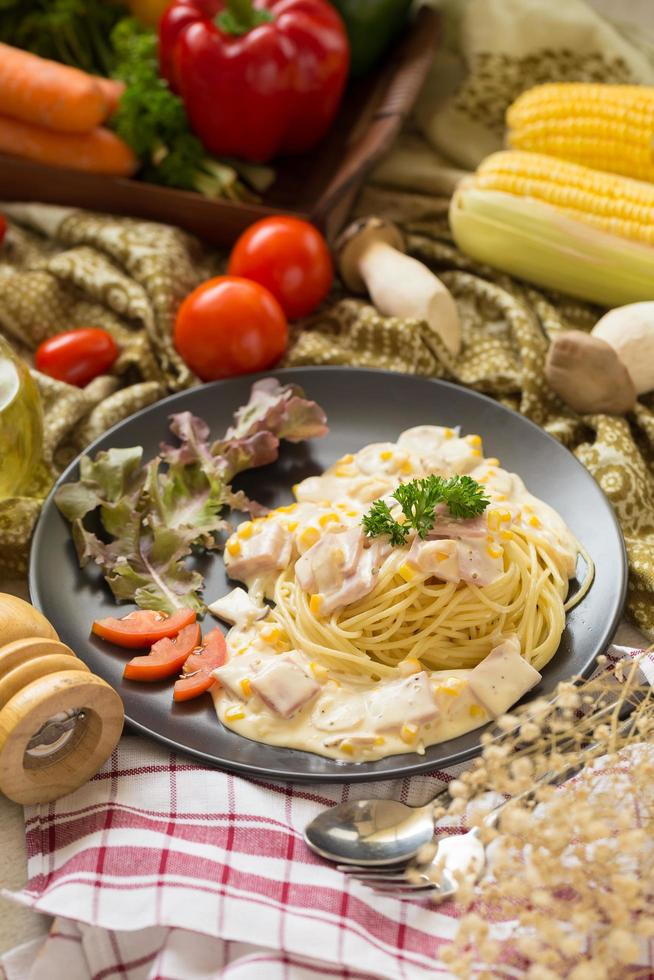 Pasta carbonara with bacon and parmesan, lettuce, and sliced tomatoes on a black dish photo