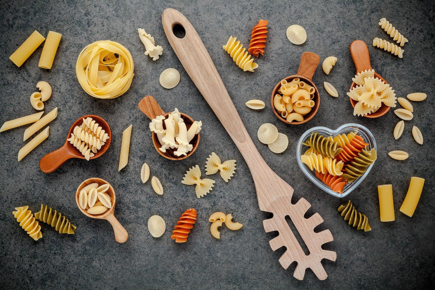 Assorted pastas and a wooden utensil photo