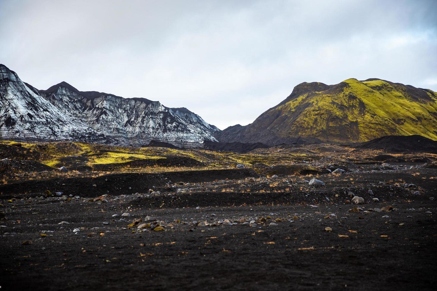 Gray and yellow mountain range across volcanic landscape photo
