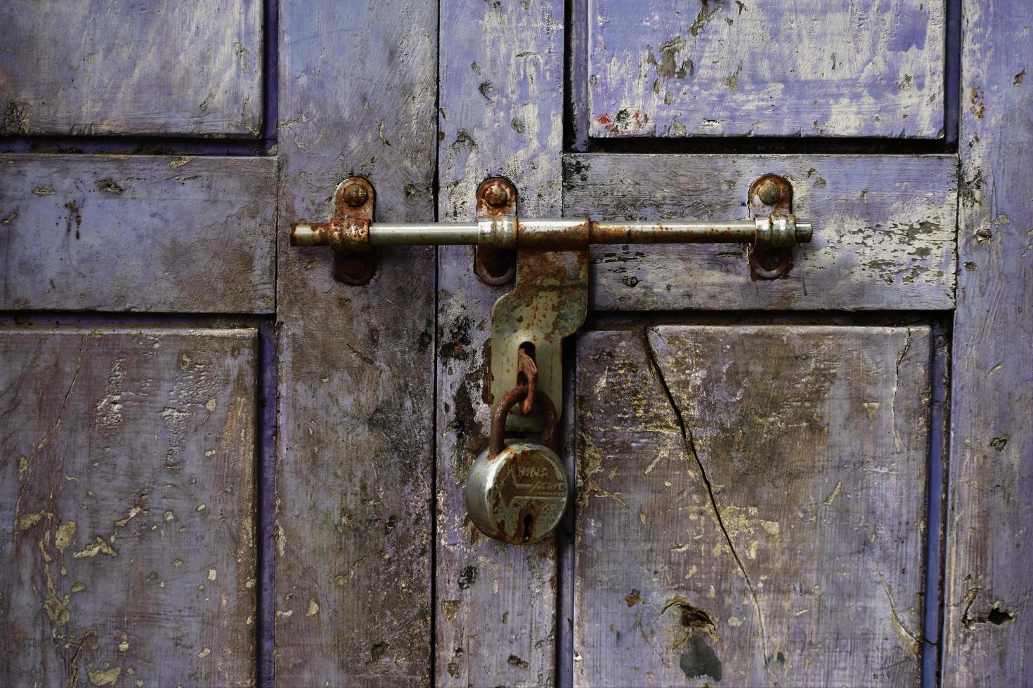 Locked padlock with a chain on a violet wooden door of an old building photo
