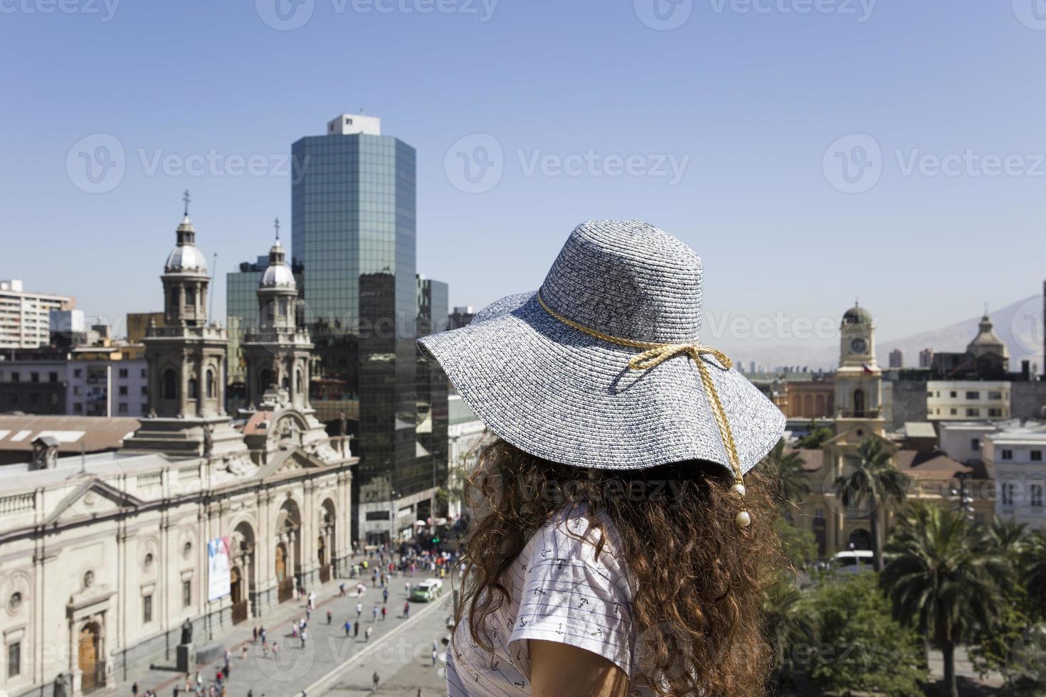 Mujer joven con sombrero mirando a Santiago de Chile. foto