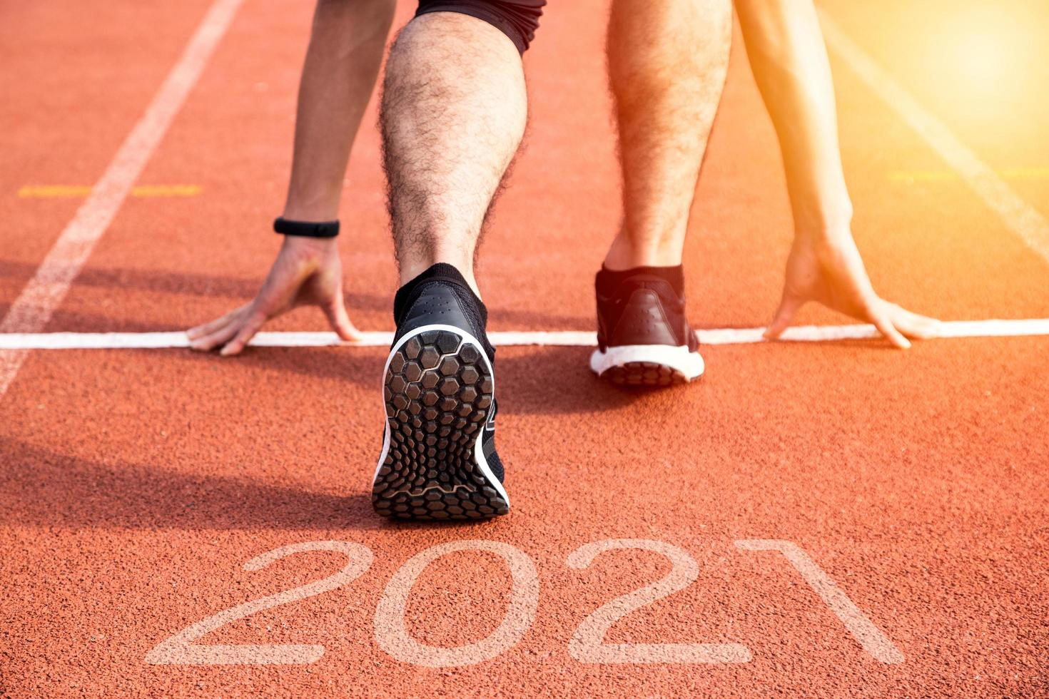 año nuevo o comenzar directamente el concepto. Cerca de un corredor atleta corriendo hacia el éxito y nuevos logros en el camino con inscripción 2021 foto
