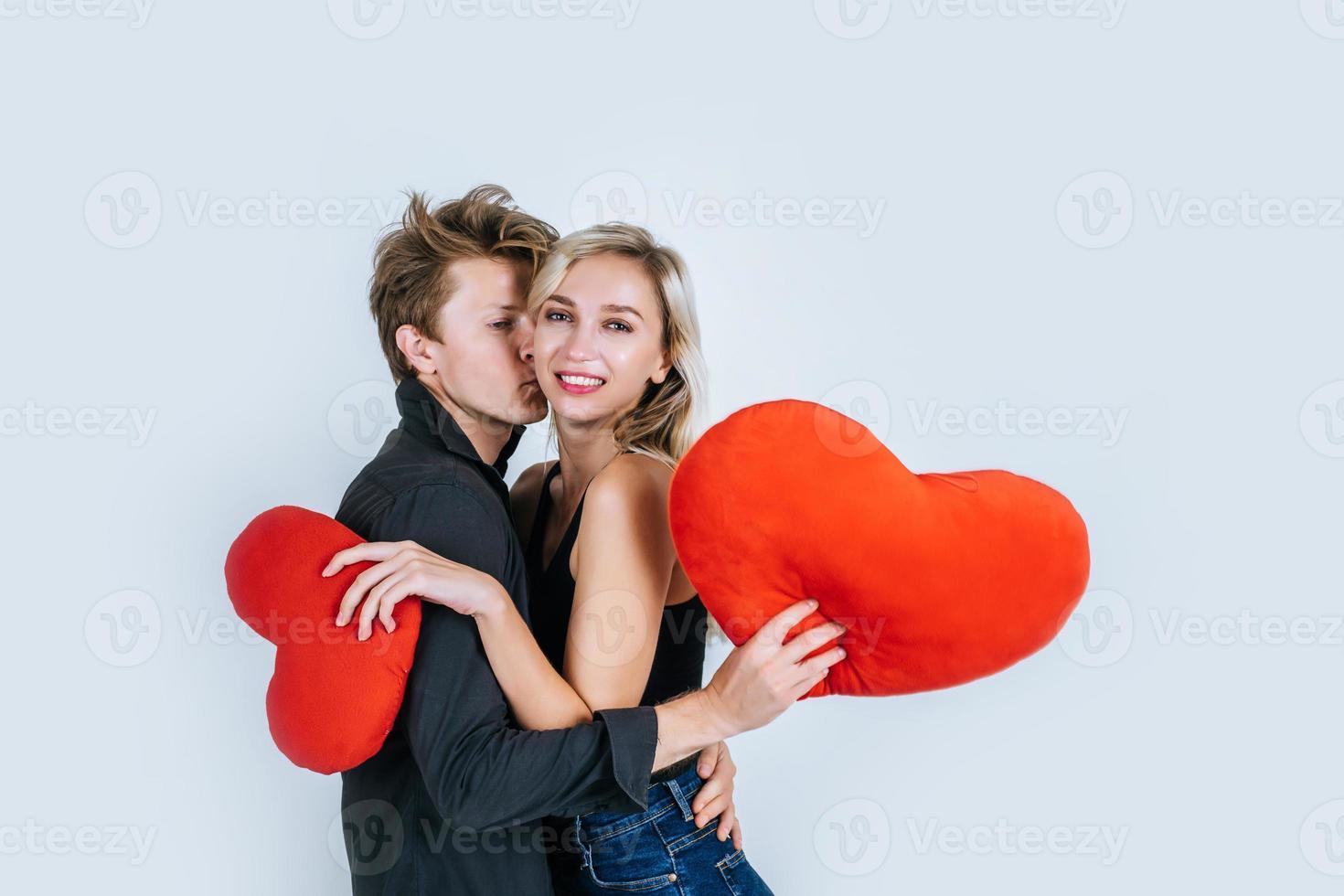 feliz pareja amorosa juntos sosteniendo un corazón rojo foto