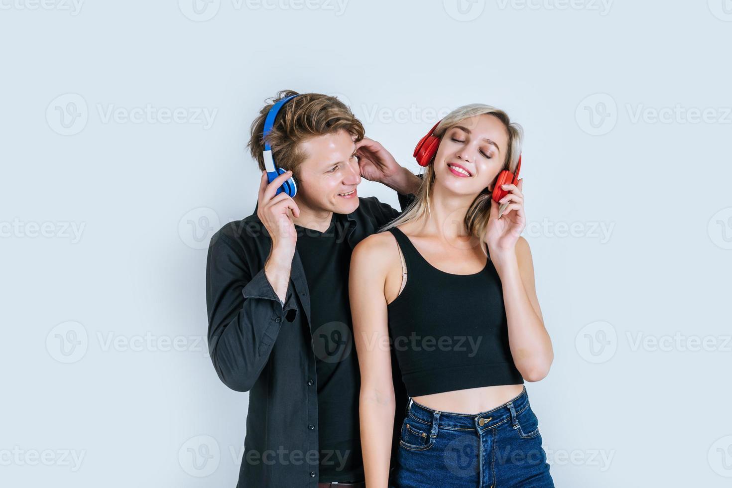 Feliz pareja joven en auriculares escuchando música en el estudio foto