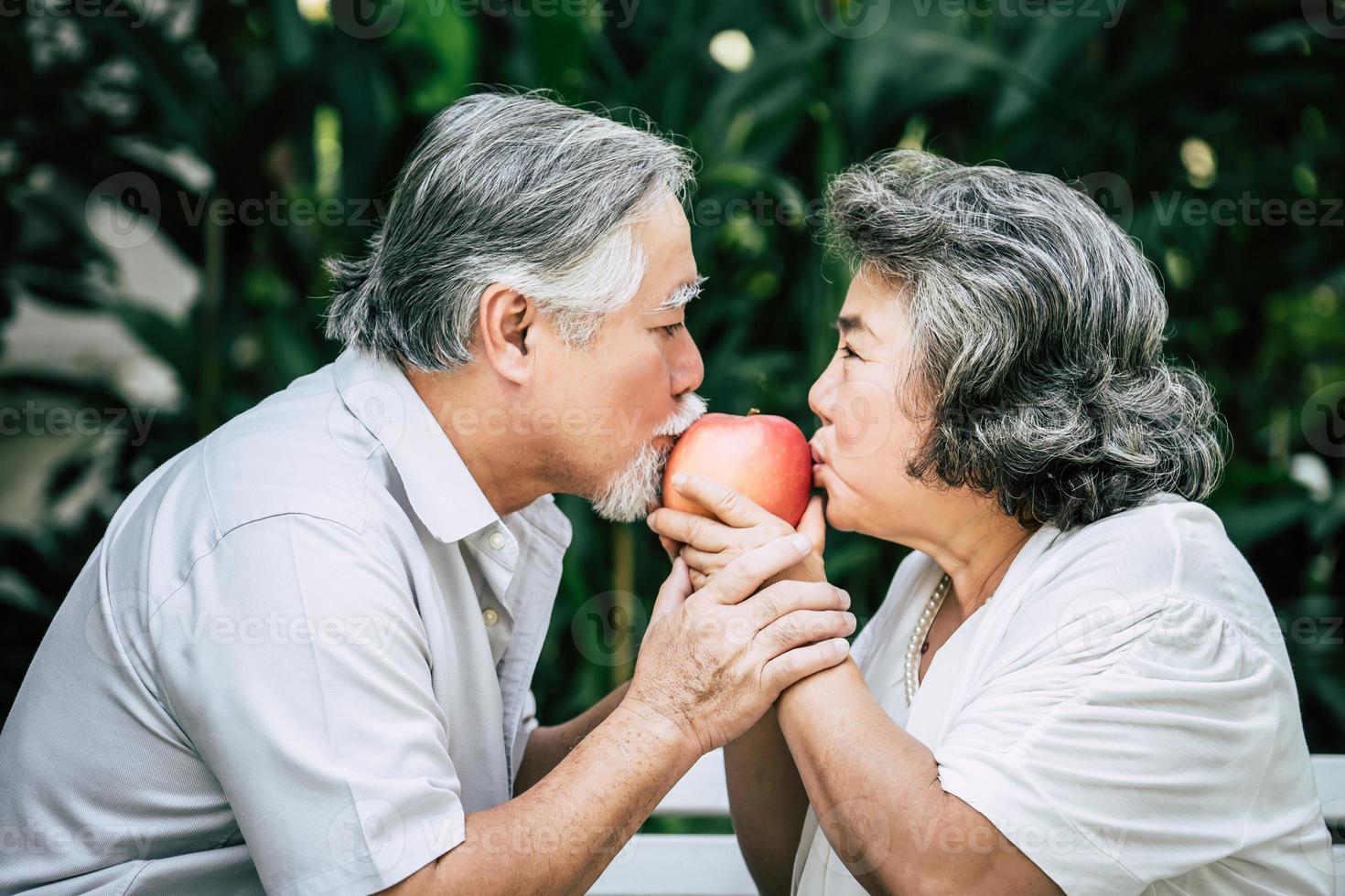 pareja de ancianos jugando y comiendo fruta foto