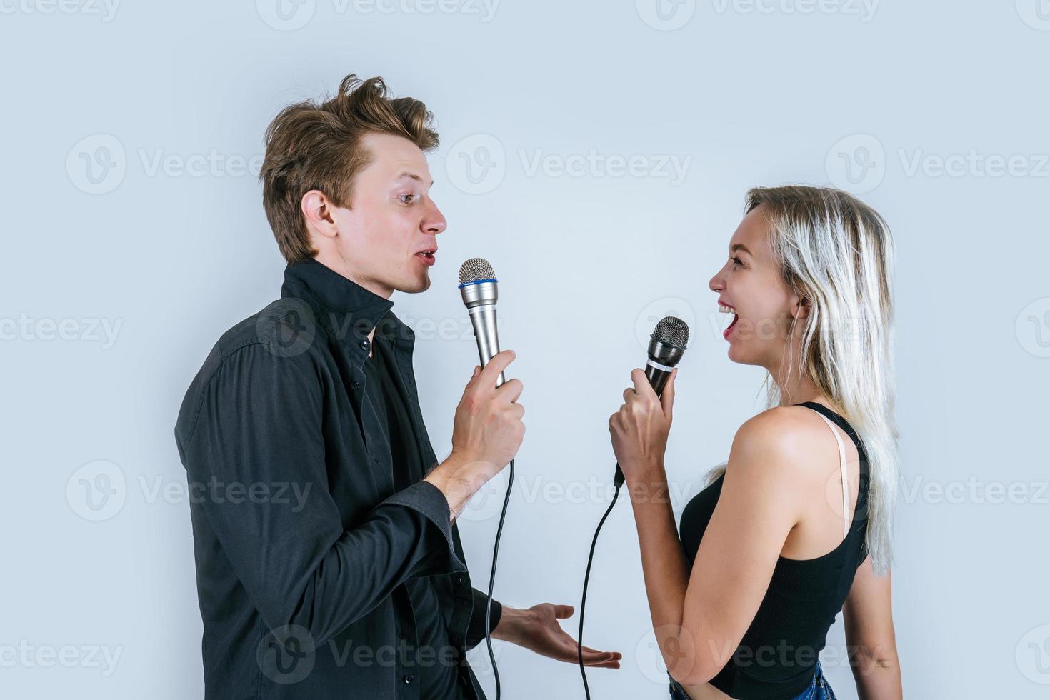 feliz retrato de pareja sosteniendo micrófonos y cantando foto