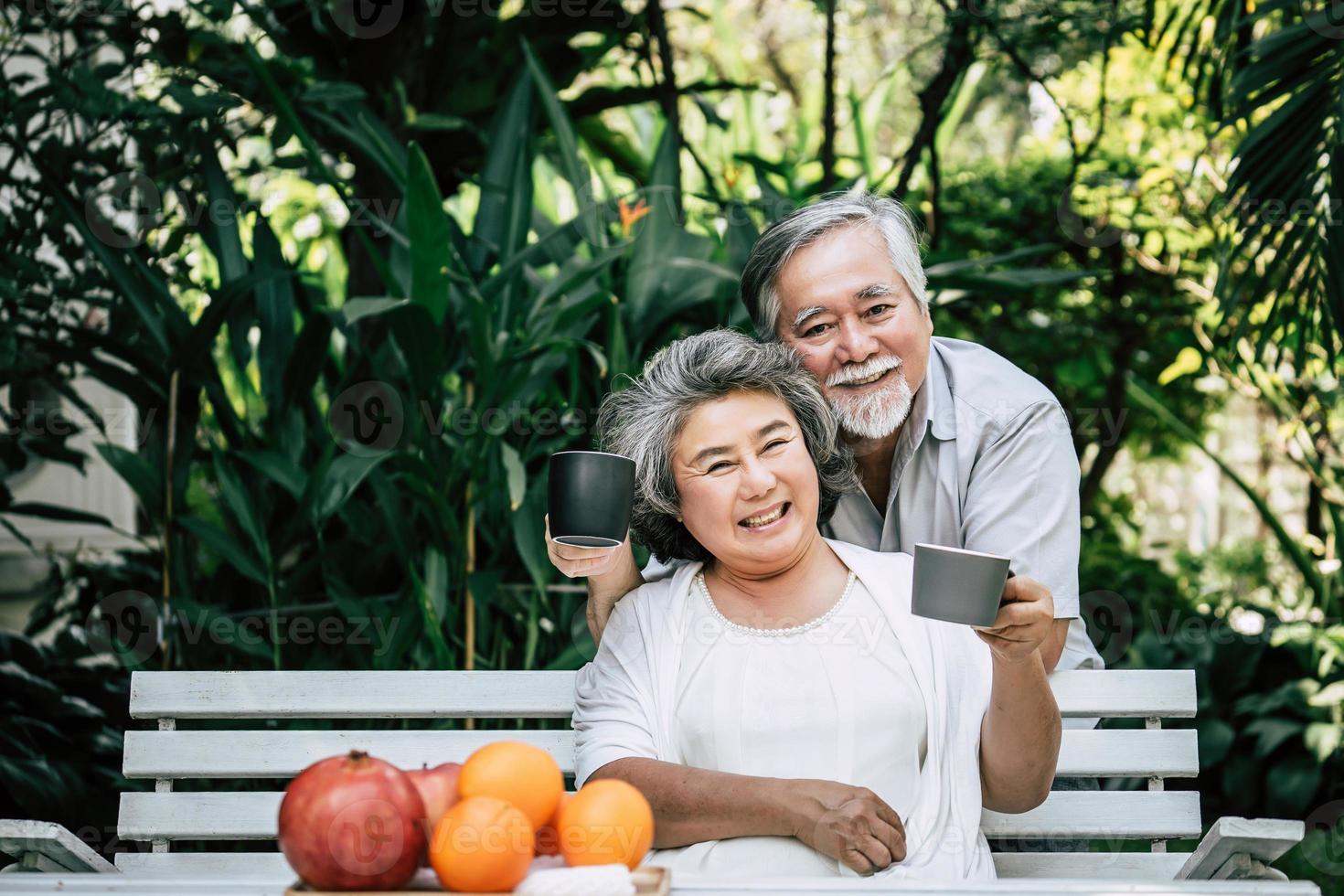 pareja de ancianos sentados y comiendo fruta foto
