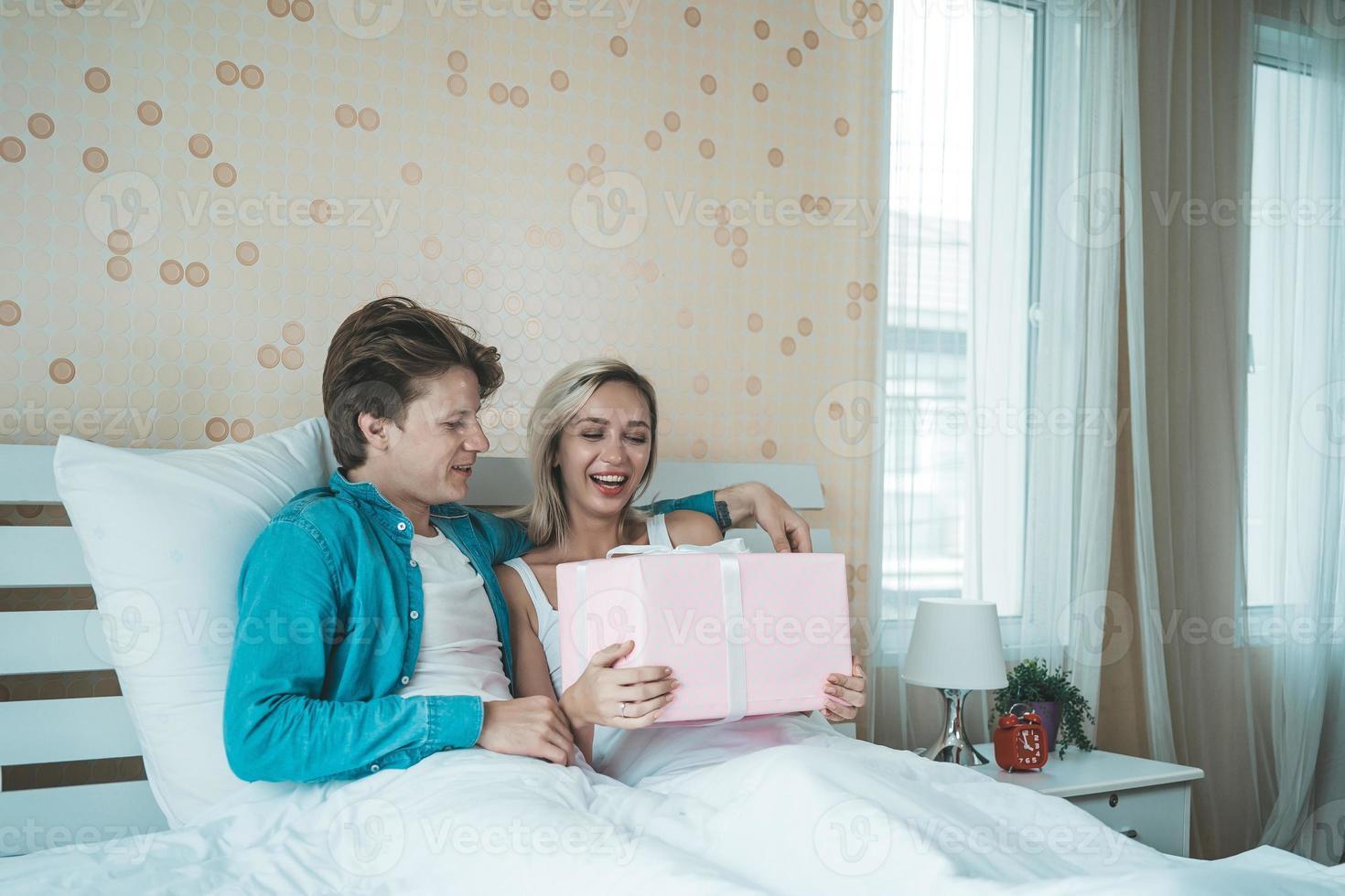 novio sorprende a su novia con caja de regalo en la cama foto