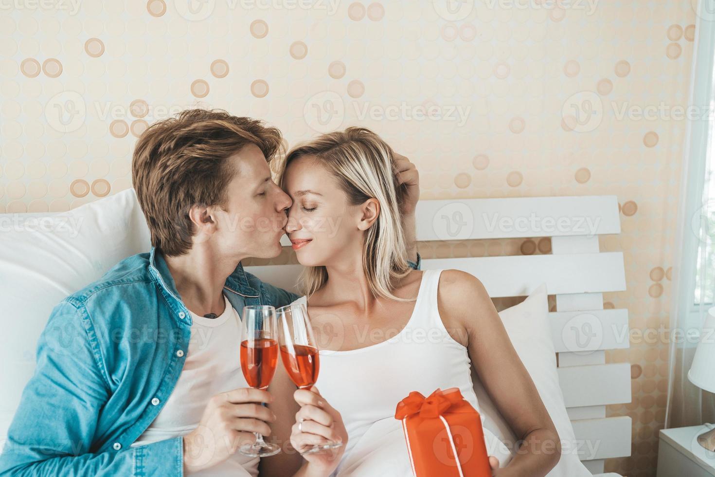pareja feliz bebiendo vino en el dormitorio foto