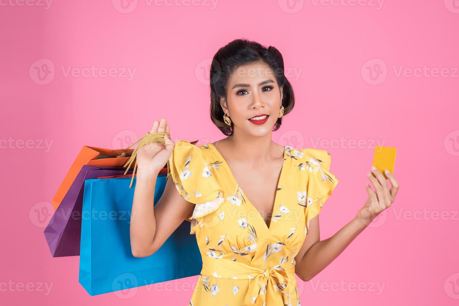 las mujeres de la moda disfrutan comprando con bolsa de compras y tarjeta de crédito foto