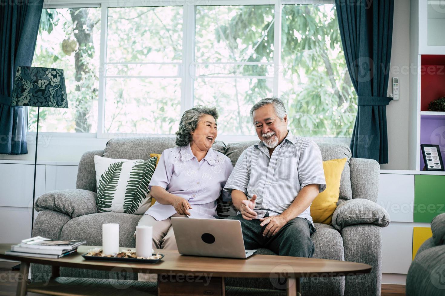 pareja mayor, hablar, y, utilizar la computadora portátil foto
