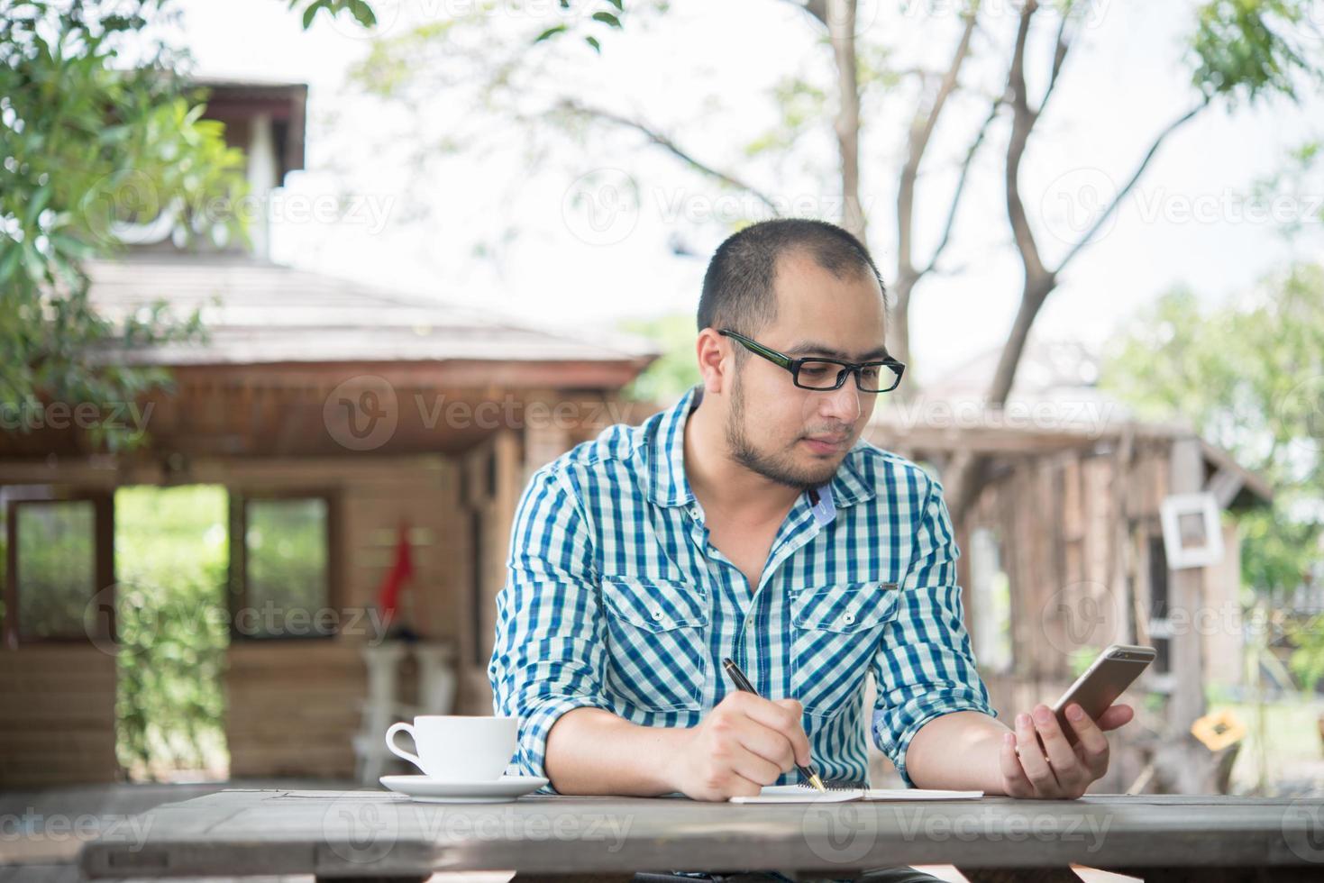 Joven empresario con smartphone mientras trabaja en el jardín de su casa foto