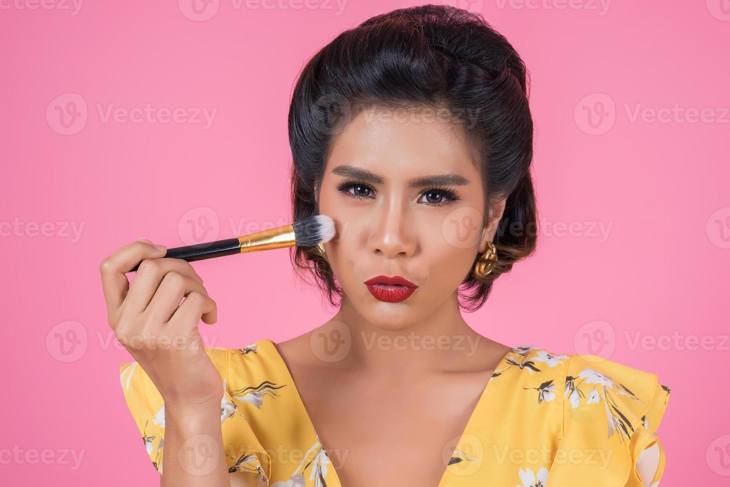 retrato de una mujer con pincel de maquillaje foto