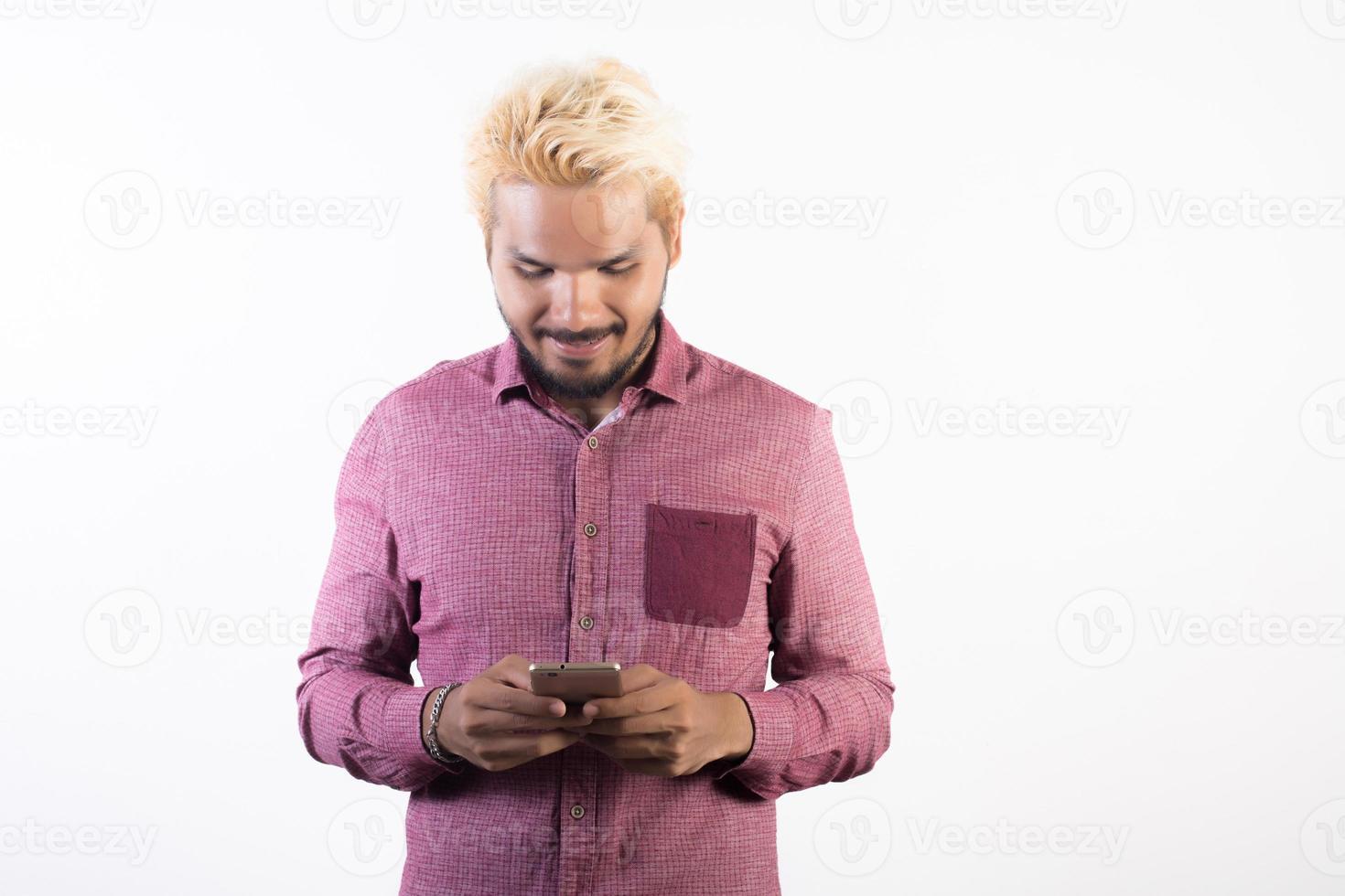 Retrato de hombre guapo con barba hipster de pie con smartphone foto