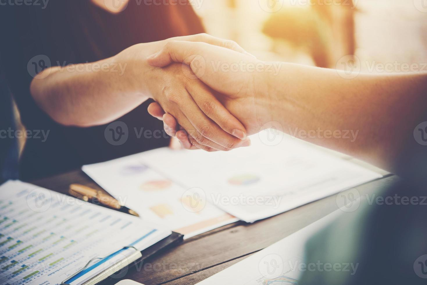 primer plano, de, dos, hombres de negocios, dándose la mano, mientras, sentado, en, el, lugar de trabajo foto