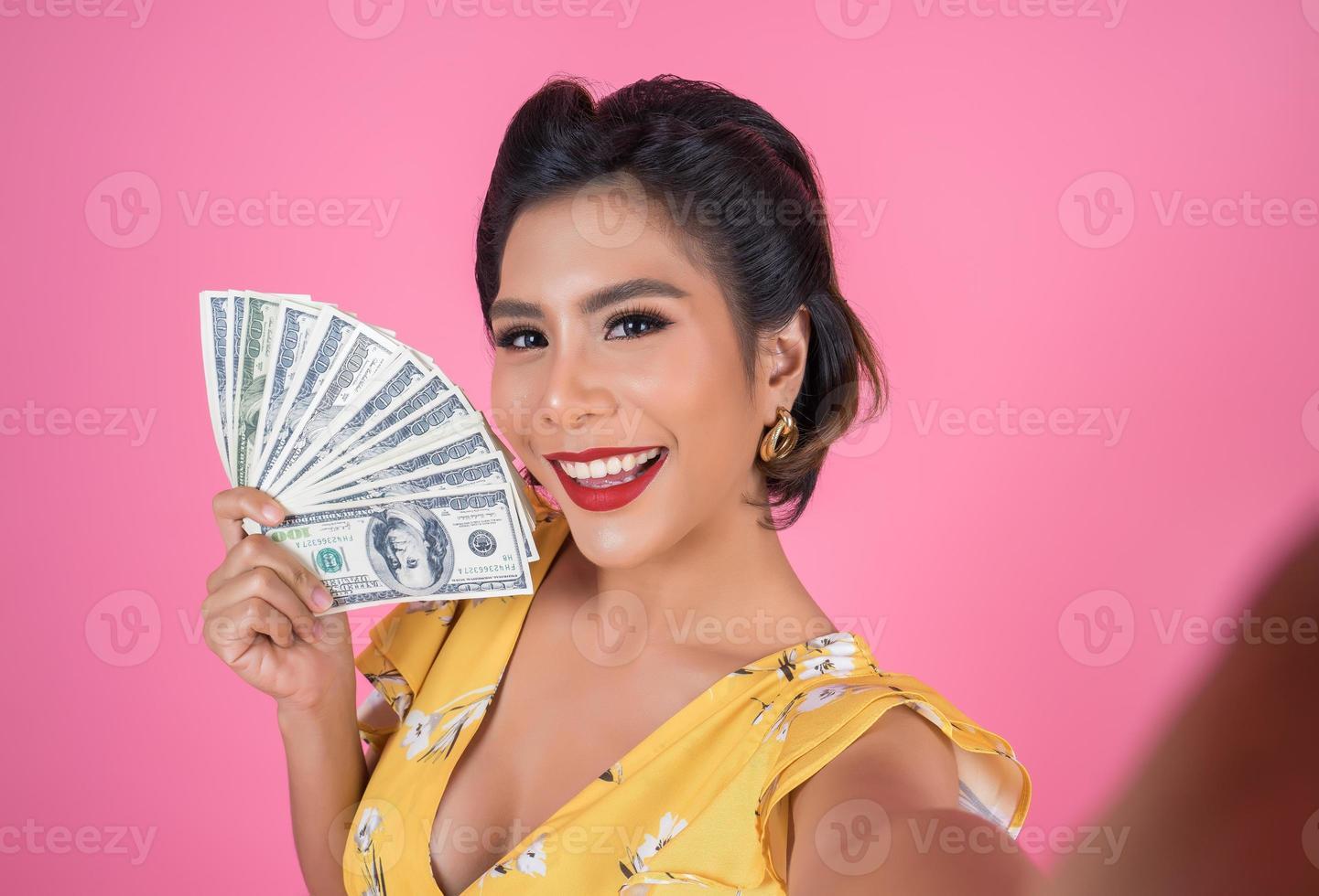 feliz mujer de moda con dinero para ir de compras foto