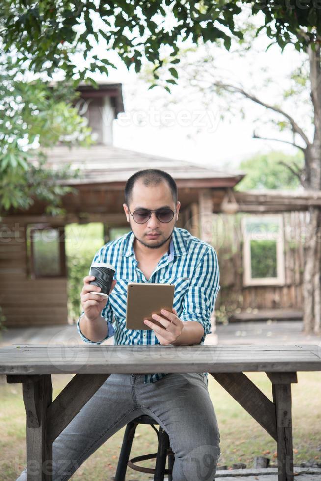 El joven se sienta al aire libre en una mesa de madera y se relaja con una tableta foto