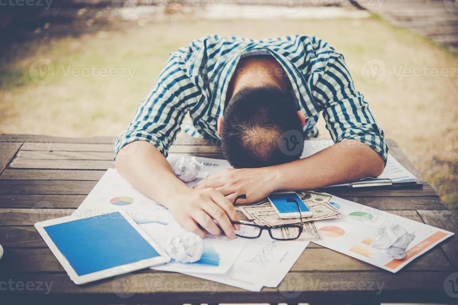 Hombre trabajador cansado durmiendo en el lugar de trabajo lleno de trabajo foto