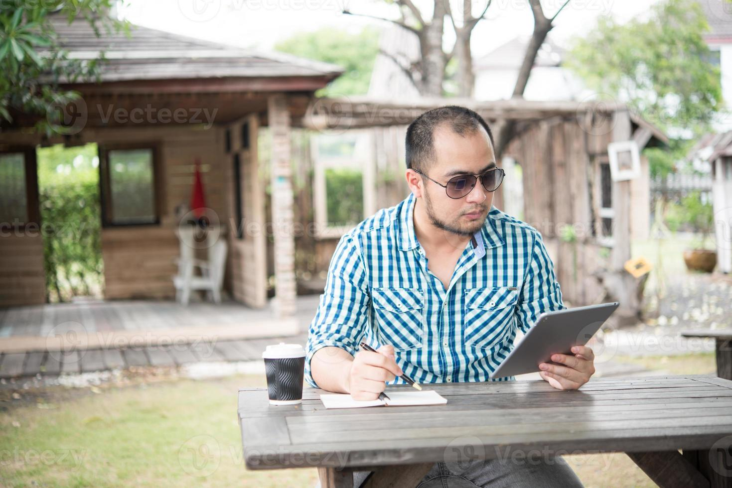 Businessman work on tablet and writing while sitting at wooden table at home photo
