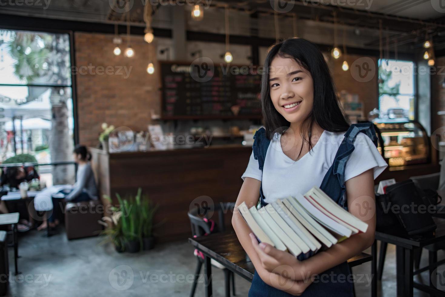 mujer joven sonriente sosteniendo libros foto